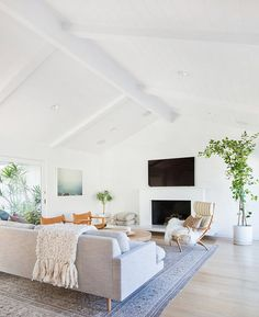 Blond woods, white walls and grey upholstery let the greenery in this mid-century living room really pop. | Photographer: Tessa Neustadt | Designer: Amber Lewis
