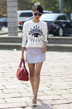 What's Kenzo's Next Big Hit?: The eyes have it in this look from Milan Fashion Week. This showgoer kept the quirky look casual and cool with an embroidered sweatshirt and a printed miniskirt finished in the eye-catching pattern. : The statement factor of this sweatshirt is staring us in the face, literally. She dressed up the cheeky graphic topper with a miniskirt and pointed-toe heels.