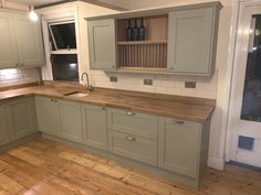 Howdens Sage Green Shaker Style. With solid oak worktops and up-stand. Under mount ceramic sink.