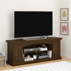 """Elevate the look of your home theater setup with this sleek, transitional Altra Portland Pier 60"""" TV Stand. Finished in a medium brown Resort Cherry, this attractive TV Stand offers a modern design that incorporates decorative rails, profiled top and antique bronze metal handles. Two doors on each end provide concealed storage for games, movies, music consoles and other entertainment essentials. The TV Stand also offers 3 center, open shelves for your cable box, DVD player and gaming…"""