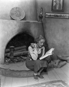 Bette Davis reading by the fireplace