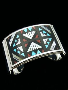 Cuff bracelet | Leander Othole (Zuni).  Sterling silver with mother of pearl, turquoise, jet and coral inlay