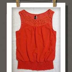 Top Bright tangerine orange sleeveless top, with a decorative neckline a d gold studs.. back has a one button closure..wide elastic bottom ruffled  hem..100%Polyester A.Byer Tops Tank Tops