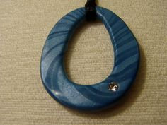 This pendant is made from blue metalic polymer clay, using a mica shift technique. It includes a small crystal to add some bling! It is strung on a black silk cord with a silver clasp. The pendant measures 2 and the cord is 20 long.