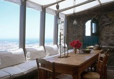 The traditional #Greek rustic #stone wall and table contrasts with the rectilinear conservatory windows overlooking the Aegean #Sea. #beach #sea #style #beachy #home #homedecor #interiordesign #architecture #interiors #relax #ocean #decorate #decorating #designerpreviews