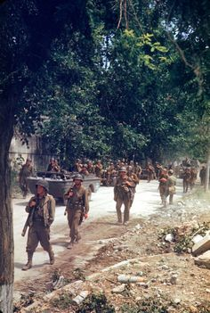 American soldiers march up the Appian Way during the drive towards Rome, WWII. I want that boat-car