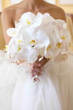 Tanya carried a bouquet composed of white phalaenopis orchids with the stems wrapped in silk ribbon. Photography: Bob & Dawn Davis Photography. Read More: https://www.insideweddings.com/weddings/chic-black-white-summer-wedding-in-chicago-illinois/369/