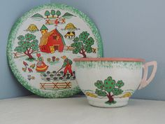 This is an adorable child/doll sized tin cup and saucer set. *The bottom states that it was made by Ohio Art, world famous for quality, Bryan, Ohio USA *The pattern is called Apple Farm, the plate features a rolling hill scenery with a barn, cow, chickens, apple tree, farmer and his wife feeding the chickens and tending to the garden. The tea cup shows wishing wells and apple trees. *I dont know the exact date of this piece, but from my online research it seems to be from the 1950s *Does...