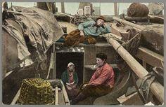 Twee Marker mannen en een vrouw, allen in dracht poserend in een botter. Verder een mand en geprinste bovendorpel. 1920-1930 #NoordHolland #Marken
