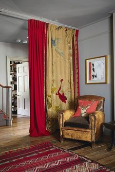 Hall in Renovated Georgian Farmhouse. Grey hall with luxurious red and gold curtain, ethnic style rug, wooden floors and leather armchair.