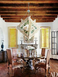 Fisher designed the dining room's light fixture, fashioned of seashells, green glass, and mother-of-pearl, and he also made the gold-leafed paintings; both the table, which has a walnut top and a hand-carved mahogany base, and the chairs are by Fisher Weisman for Michael Taylor Designs. The floor tiles were hand-rubbed with gasoline and tar to create a patina.