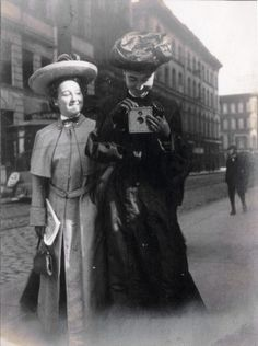Two women visitors for the 1904 World's Fair in downtown St. Louis. One taking a photo with a box camera.