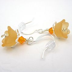 Soft, but a little bit flirty, these peach lucite bell flowers swing beneath decorative bright silver leaf bead caps. Perched atop this are tiny orange Swarovski crystals. From the center of the flowe