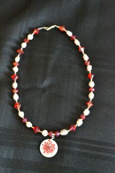Fun necklace with pearly shell style beads and orangy red glass beads.  Pendant is a similar shell type with actual reddish flower designed into it.  $17