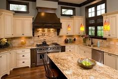 Cream Cabinets with brown glaze, dark accents (LOVE the hood!), tan granite countertops, wood flooring, stone backsplash behind stove. could do this to get bigger stove in kitchen remodel a way to work with our cream distressed cabinets.