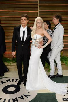 The stunning duo actor Nolan Gerard Funk and Lady Gaga at the Vanity Fair After Party. Lady Gaga wore absolutely gorgeous custom-made Atelier Versace floor length gown and Nolan wore a Versace black tuxedo. #VersaceCelebrities #Oscars2014