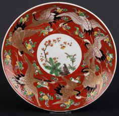Description A Japanese Arita porcelain saucer dish decorated in overglaze enamels and gilding with Manchurian Cranes with stylised clouds on a brick-red ground, surrounding a central roundel of The Three Friends (bamboo, pine and prunus), the reverse is plain  Date 1880-1910  www.collectorstrade.de