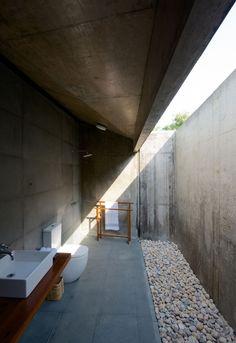 badezimmer außenbereich kieselsteine betonwände glasdecke spalte