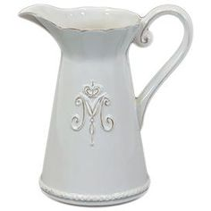 """Gently weathered pitcher with swirl and crown detail.   Product: Pitcher  Construction Material: Ceramic  Color: White    Dimensions: 9"""" H x 8.5"""" W x 5.5"""" D       Note: This item has a distressed finish.  Each piece will have an antiqued look all its own."""