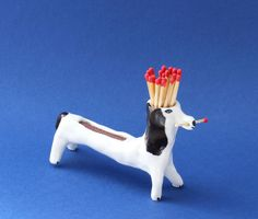 This is a matchstick dog to help you lit you candles when the evening come.  Its a uniquely hand-sculpted dog, made out of paper porcelain, covered with a satin transparent glaze and hand-painted details. He comes with matchsticks ready to use.  The dog is about 7 cm high and 11 x 3 cm wide and weighs 100 g.  This item is completely handmade and one of a kind.   ———— Please be sure to read my store policies before making a purchase.  Shipping takes up to 20 days. All International shipping…