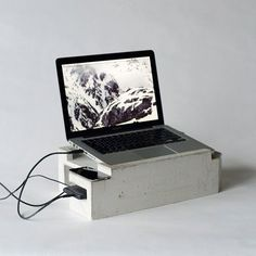 A concrete laptop stand with underground parking for an external hard drive