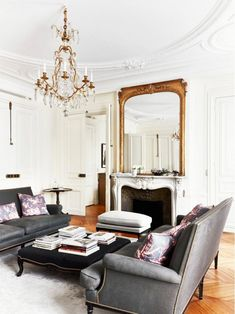 love this living room - grey couch, gold mirror, white walls, and chandelier