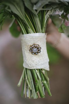 lace wrapped bridesmaid bouquet with small brooch #bouquet #brooch #lace http://www.weddingchicks.com/2014/01/21/good-mood-metallic-wedding/
