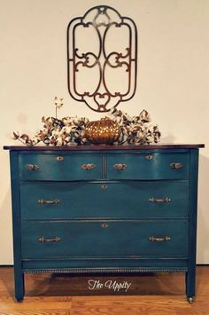 """Love your stains. Recently did a dresser in an Annie Sloan mix but the top is the show stopper. I created a faux burl effect with a couple of your stains. It worked out fabulously. I used the water-based Orange Dye Stain first, then proceeded to use Candlelite and Java Gel Stains to aid in the burl effect!"" - Tammy Sue of The Uppity To achieve the teal-blue that has been created for the base, GF would recommend mixing Coastal Blue and Patina Green Milk Paint."