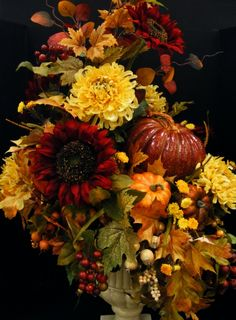 Pumpkins nestle together surrounded by fall leaves, berries, sunflowers and mums. Annette at Michaels Arts & Crafts Madison, TN
