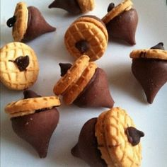 "{Acorn Cookies} Mini Nutter Butter Cookies on the Bottom of Hershey Kisses Topped Off with a Chocolate Chip ""Stem"".  All held together with Melted Chocolate as the ""Glue""!!! BRILLIANT! EASY! ADORABLE! I'm in!!!"