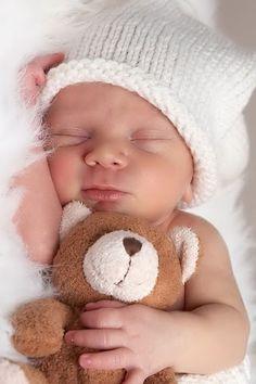 Sur cette image, on voit un bébé couché sur le côté sur des plumes et il tient un ours en peluche brun dans ses bras.Le bébé porte un chapeau blanc et a les yeux fermés.J'ai choisi     cette image parce que je trouve que les bébés sont mignons, mais aussi parce que cela me rappelle ma petite soeur quand elle était petite ainsi que lors ce que je jouais à la poupée.
