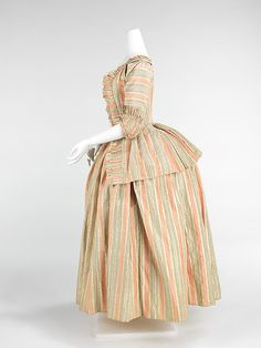 "Dress, 1775, French, silk. ""This is an example of one form of dress which became acceptable in the later part of the 18th century. The bodice is more like a jacket, known as a caraco. The informal sensibility about it is relative to the open robes and exposed petticoats of the period. The sleeves are known as sabot sleeves because they fit over the elbow like a sabot shoe or clog"". Met Museum"