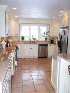 white cabinets, gray and wood counters, and terracotta floors