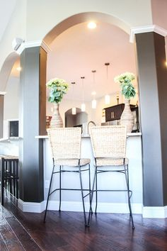 Kitchen-  Bar Stools idea (wicker seat/expresso legs) Lowe's Vases with flowers at ends of breakfast bar