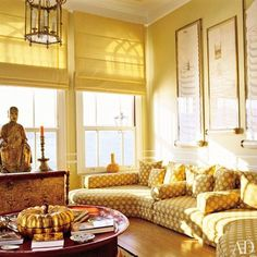 In an ochre-hued Turkish sitting room by designer Barbara Ther, a Buddha sits in front of a window overlooking the Bosporus Strait. Framed sultanic decrees, examples of the homeowner's passion for Islamic calligraphy, hang above a patterned sectional sofa. (April 2006)