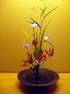 This is a traditional Japanese-style ikebana arrangement. Usually, Japanese flower arrangements have uneven numbers of flowers, such as, one of a kind, 3 of a kind, 5 of a kind, and so on. Also, typically there are 3 types of flowers or foliage used. nice