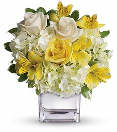 White hydrangea, yellow roses, crème roses and yellow alstroemeria accented with fresh greenery