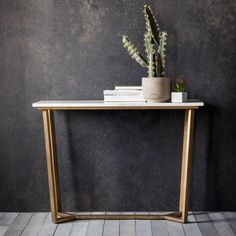 Cleo Marble Console Table   A contemporary console table with a white volkas marble top featuring subtle natural tones in the grain and a brushed bronze angled metal base.