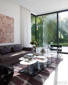 The cocktail table in this family room is by Bismut & Bismut, the hanging glass sculpture is by Jean-Michel Othoniel, and the rug is by Toyine Sellers.
