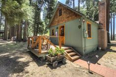 This a 600 sq. ft. Wildflower cabin in California. Outside, you'll notice a standard gable roof with vertical green siding mixed with cedar shakes. A real brick fireplace stands on the side a…