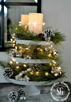 tiered cake stands with white berries, pinecones, pine garland, lights and candles...love