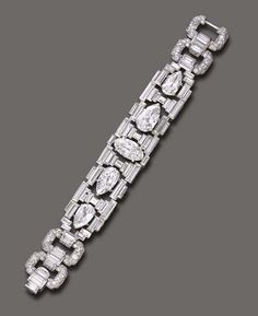 A MAGNIFICENT ART DECO DIAMOND BRACELET, BY CARTIER  The openwork baguette-cut diamond geometric band, of flexible design, centering upon a marquise-cut diamond, weighing approximately 7.19 carats, flanked on either side by pear-shaped diamonds, weighing approximately 7.03, 6.24, 4.98 and 3.76 carats, joined by pavé-set diamond links and baguette-cut diamond arched spacers, mounted in platinum, circa 1927