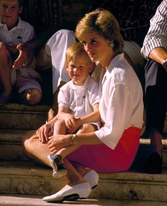 Diana, Princess Of Wales, sits on the steps of the Marivent Palace with Prince Harry during their summer holiday in Palma, Spain, on August 13, 1998