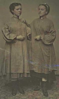 Dark photograph of 2 young women wear work smocks over street clothes. Showing there high top shoes.