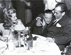Peter Lorre being hugged by Humphrey Bogart as Lauren Bacall looks on.