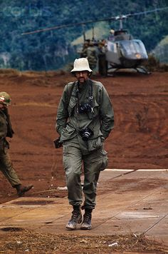 02 Feb 1971, Khe Sanh, Vietnam. UPI staff photographer Kent Potter is shown walking and there are GIs' and a helicopter behind him