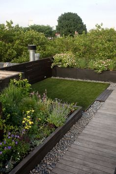 artificial turf grass lawn area, shrubs and flowers in raised beds, gravel and board paths in rooftop garden by Julie Farris, NYC