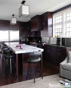Mahogany is used extensively in the kitchen, where a stainless steel backsplash harmonizes with a Wolf range.