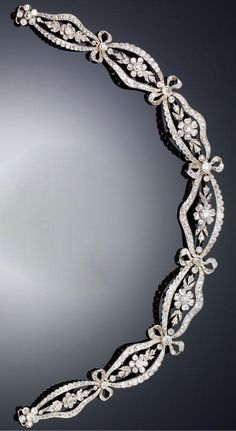 A BELLE EPOQUE DIAMOND DIAMOND COLLIER DE CHIEN/BANDEAU, CIRCA 1910. In the garland style, designed as a graduated series of scalloped oval plaques each centring on a floral motif and interspersed with ribbon tied bows, millegrain-set with circular- and rose-cut diamonds, length approximately 280mm, loop attachments to reverse, accompanied by a bandeau frame.