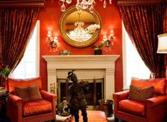 LIVING ROOM: A space worthy of any castle.  Red and orange with white fireplace, luxurious heavy drapes, and crystal sconces.